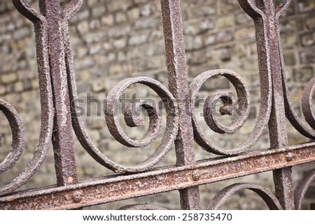 Iron rusty fence closeup with brick wall in background. - stock photo