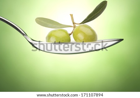Iron Spoon with olive oil close up on a green background - stock photo