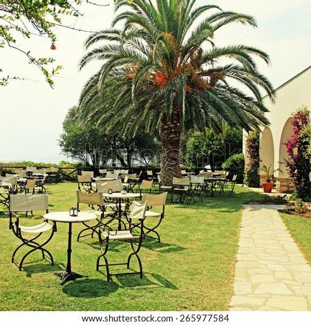 Iron tables and chairs on green lawn in the garden with flowers, palm tree and sea view(Greece), square toned image, instagram effect - stock photo