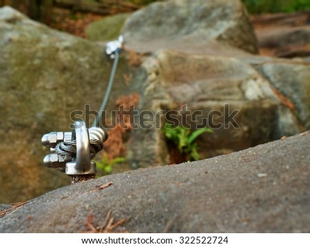 Iron twisted rope stretched between rocks in climbers patch.  Rope fixed in block by screws snap hooks. Detail of rope end anchored into sandstone rock - stock photo