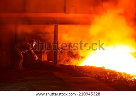 iron works blast furnace taphole spewing molten iron, closeup of photo - stock photo