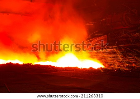 iron works blast furnace taphole spewing molten iron, closeup of photo - stock photo