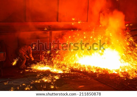 iron works blast furnace taphole spewing molten iron, closeup of photo