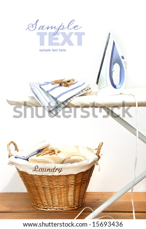 Ironing board with laundry against white background
