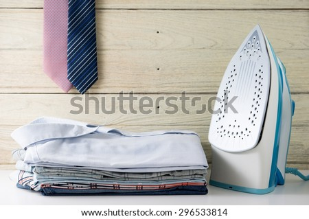 Ironing clothes laundry housework with stack of shirts and tie hanging - stock photo