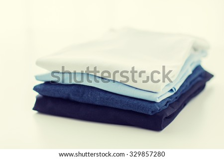 ironing, laundry, clothes, housekeeping and objects concept - close up of ironed and folded t-shirts on table at home - stock photo