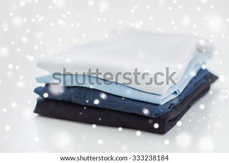 ironing, laundry, clothes, housekeeping and objects concept - close up of ironed and folded t-shirts on table at home over snow effect - stock photo