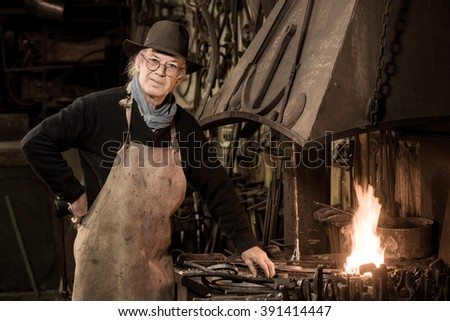 Ironworker forging hot iron in workshop