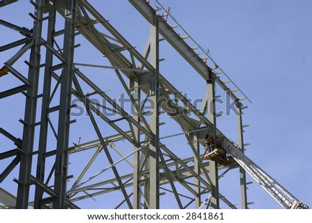 ironworkers erecting structure with aide of crane