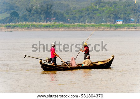 IRRAWADDY RIVER, MYANMAR - AUG 26, 2016: Unidentified Burmese peope in a wooden boat over the Irrawaddy River, Myanmar. It's largest rive and most important commercial waterway
