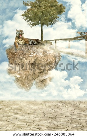 irreal image: Tiger lying on a floating rock, aggressive expression because a hunter with a gun pointed - stock photo