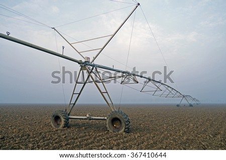 irrigate a crop with winter fog - stock photo