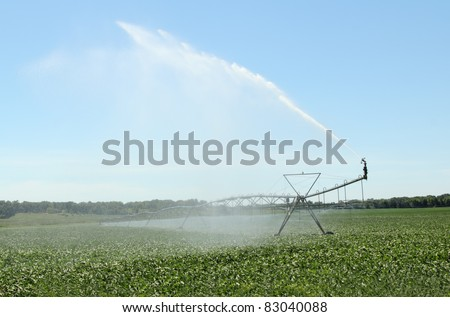 Irrigating a farm field of soybeans - stock photo