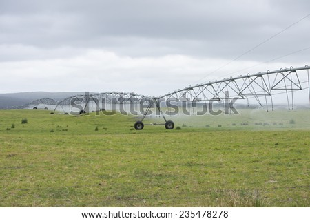Irrigation by pivot sprinkler and spraying system on green grass field or meadow on rural agricultural farm land, copy space. - stock photo