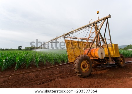 Irrigation equipment watering a crop of corn. - stock photo