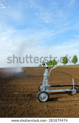 Irrigation in the field with a sprinkler - stock photo
