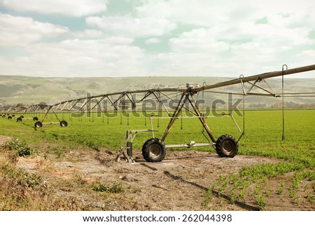 Irrigation of farmland. Warm toned effect - stock photo