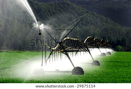 Irrigation pivot system watering a field - stock photo