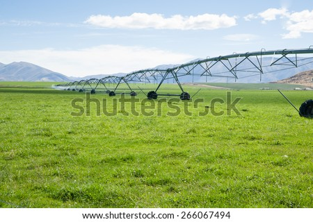 Irrigation system, long moveable booms of the water distribution plant stretches across farming fields on Otago, New Zealand. - stock photo