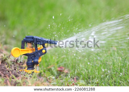 irrigation system moistening land for growing green lawn - stock photo