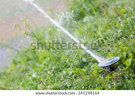 Irrigation system sprinkler head watering green grass lawn  - stock photo