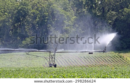 Irrigation system watering a farm field of soybeans