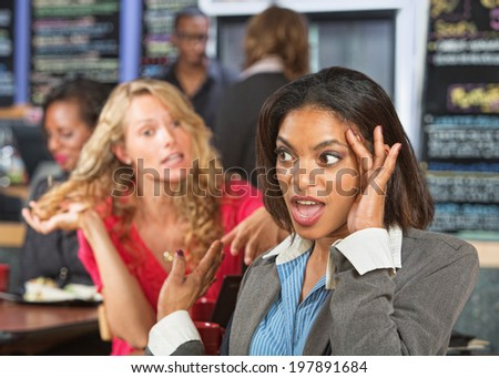 Irritated business woman listening to emotional lady - stock photo