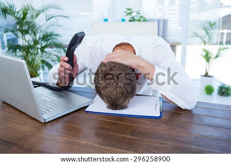 Irritated businessman holding a land line phone in the office - stock photo