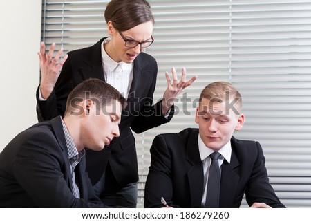 Irritated businesswoman and her colleagues at business meeting - stock photo