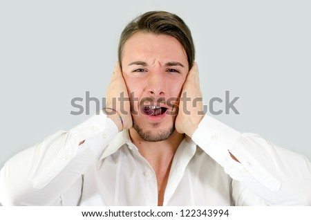 Irritated, frustrated, stressed guy covering his ears, too much noise - stock photo