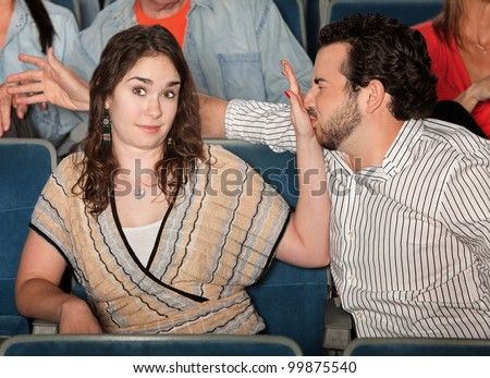 Irritated girlfriend stops misbehaving boyfriend in theater - stock photo