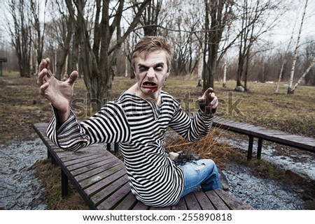Irritated scary guy sitting on the bench - stock photo