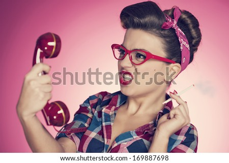 Irritated smoking pin-up girl with retro telephone