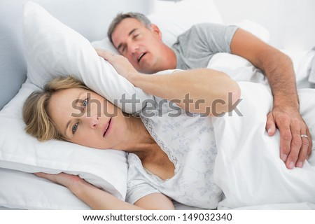 Irritated wife blocking her ears from noise of husband snoring in bedroom at home - stock photo