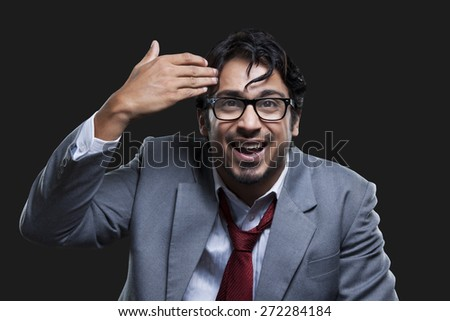 Irritated young businessman gesturing against black background