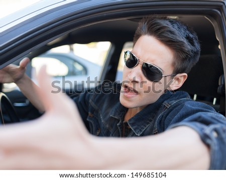Irritated young man driving a car. Irritated driver - stock photo