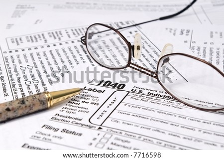 IRS 1040 forms with pen and glasses