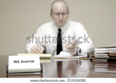 IRS tax auditor man with a stern or mean expression - stock photo