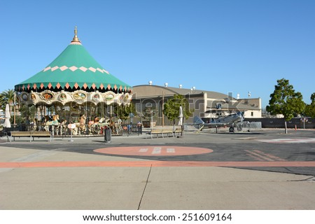 IRVINE, CA - FEBRUARY 10, 2015: The Orange County Great Park Carousel Ride, with vintage airplane and hangar. The park is being built on the former Marine Corps Air Station, El Toro. - stock photo