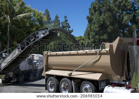 IRVINE, CA - JULY 23, 2014: Irvine's residential street rehabilitation and slurry seal project began with pavement recycling vehicles and crew removing the top layer of deteriorated asphalt.
