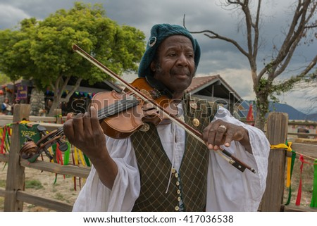 Irwindale, CA - USA - May 07, 2016: Man with medieval costume fiddling during The 54th Annual Renaissance Pleasure Faire.
