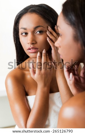 Is it acne? Concentrated young African woman touching her face and looking at herself in a mirror  - stock photo