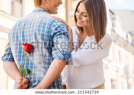 Is it for me? Rear view of young man holding red rose behind his back while woman walking in the background  - stock photo