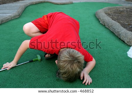 Is It In There?  A little boy looks into the cup in the last hole of mini-golf - stock photo