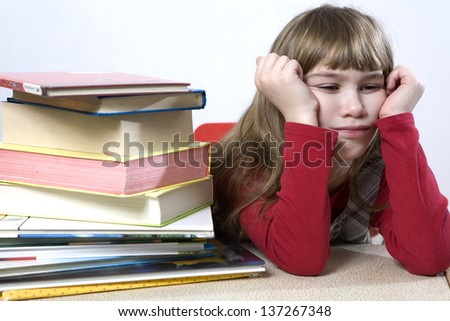 Is it possible to read all these books? little cute sad  girl with a pile of book sitting at table. - stock photo