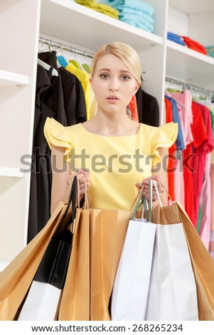Is not it too much. Vertical shot of an anxious young shopaholic holding paper bags in a fashion store - stock photo