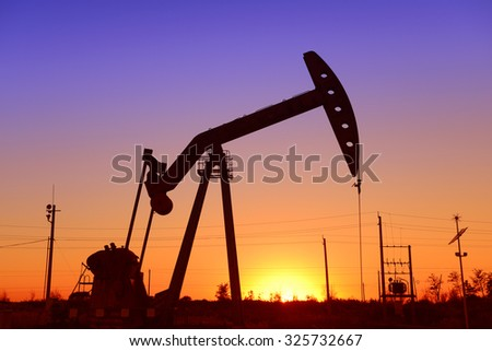 Is operation of the pumping unit in oilfield sunset, close-up