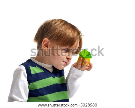 Is that my dream house? Cute 3-yeas old boy looking to small house built from wooden blocks. - stock photo