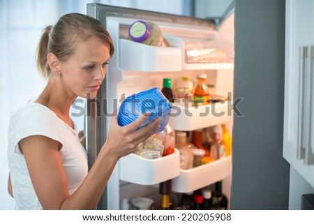Is this still fine? Pretty, young woman in her kitchen by the fridge, looking at the expiry date of a product she took from her fridge - - stock photo