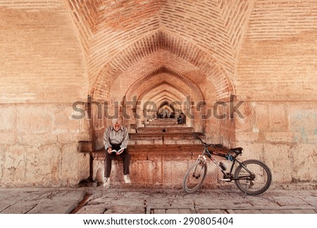ISFAHAN, IRAN - OCT 15: Old man read a novel with his bicycle under the famous Khaju Bridge on October 15, 2014. Great example of Persian architecture, Khaju Bridge was built by ShahAbbasII in 1650 - stock photo
